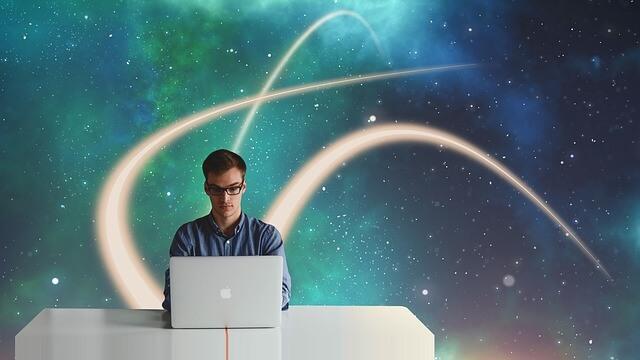 Mężczyzna siedzi przy laptopie na tle galaktyki