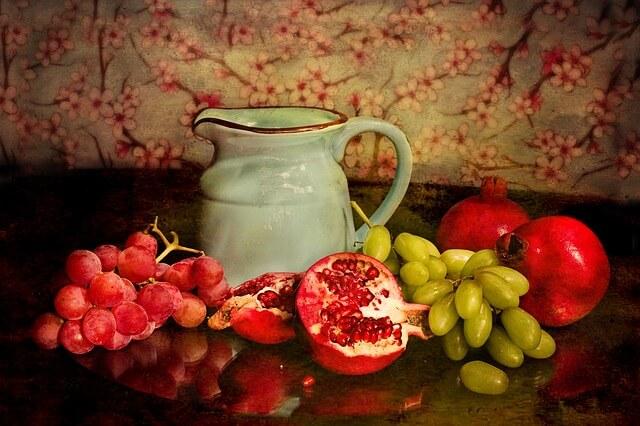 Dzbanek, obok granat i czerwone winogrona