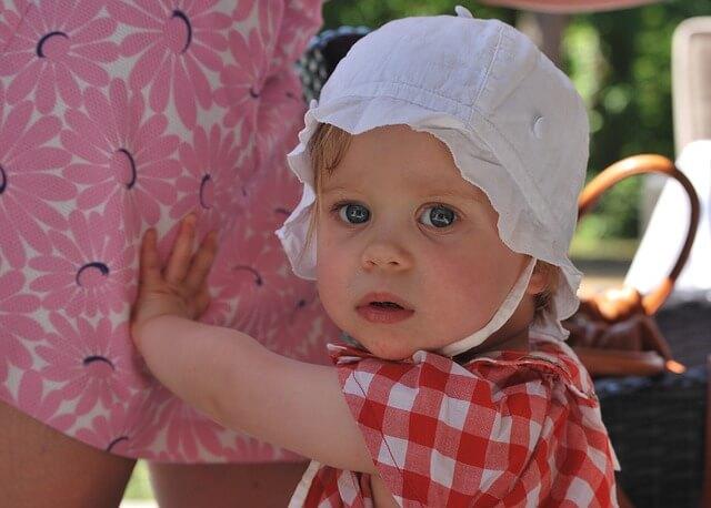Dziecko w białym kapelusiku i koszulce w czerwoną kratkę