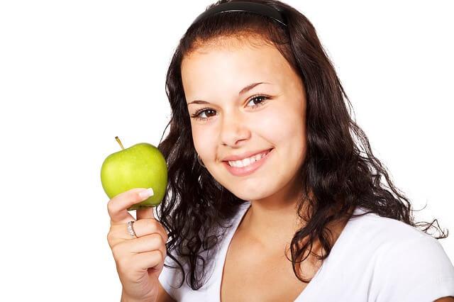 Dziewczyna trzyma w ręce zielone jabłko