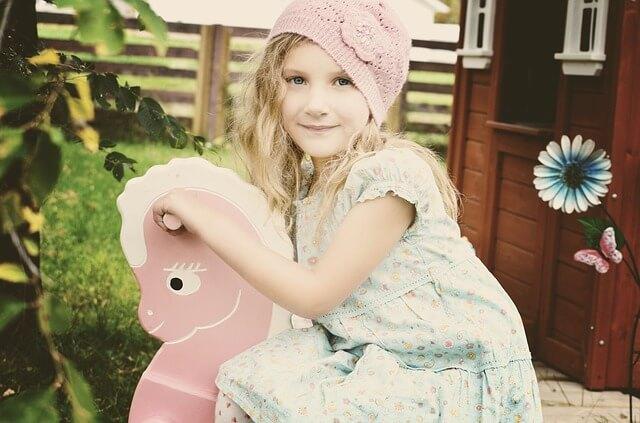 Dziewczynka na różowym koniku bujanym