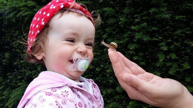 Dziecko wróżowym śliniaczku trzyma w buzi smoczek
