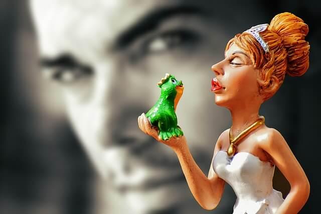 Figurka kobiety trzymającej w ręce żabę na tle zdjęcia mężczyzny