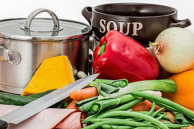 Garnki na zupę wśród papryki i pora