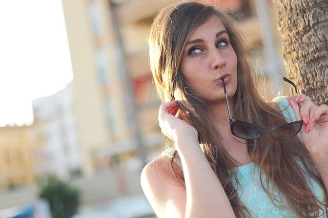 Kobieta dotyka do swoich włosów, w ustach ma zausznik okularów przeciwsłonecznych