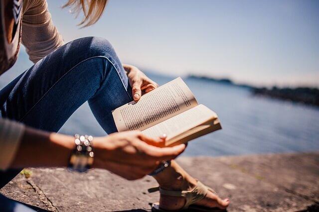 Kobieta siedzi nad morzem i czyta książkę