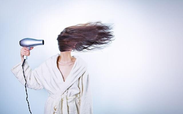 Kobieta susząca włosy suszarką
