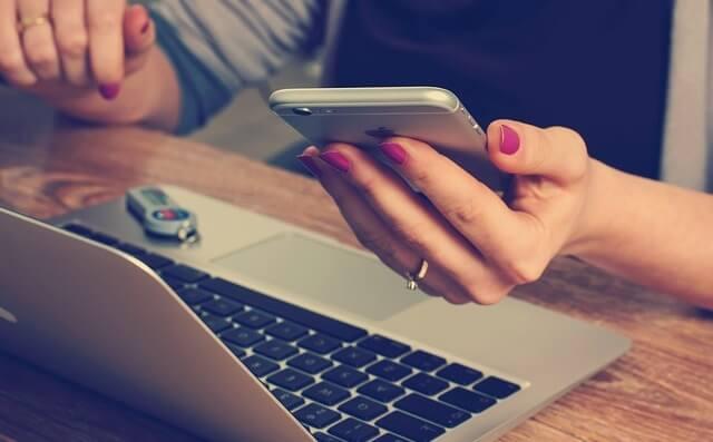 Człowiek pracujący przy komputerze i z telefonem w ręce
