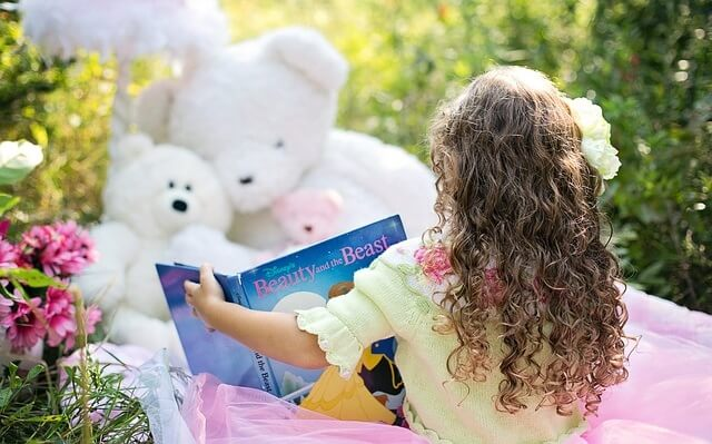 Dziewczynka z książką i pluszakami