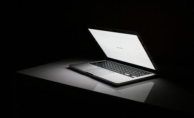 Włączony laptop leżący w ciemności