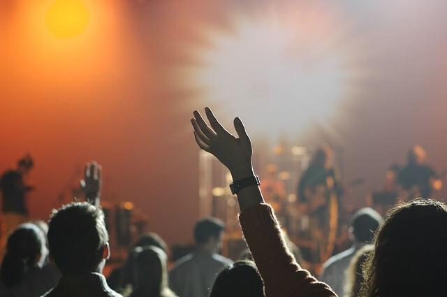 Ludzie z rękami uniesionymi podczas koncertu