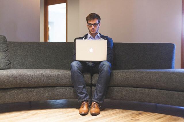 Mężczyzna siedzi na kanapie i pisze na laptopie