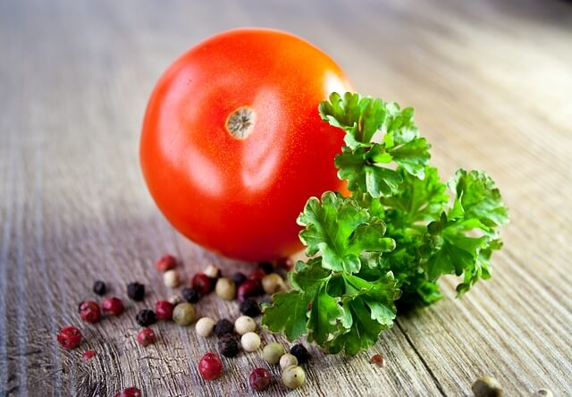 Pomidor, obok kolorowy pieprz i oregano