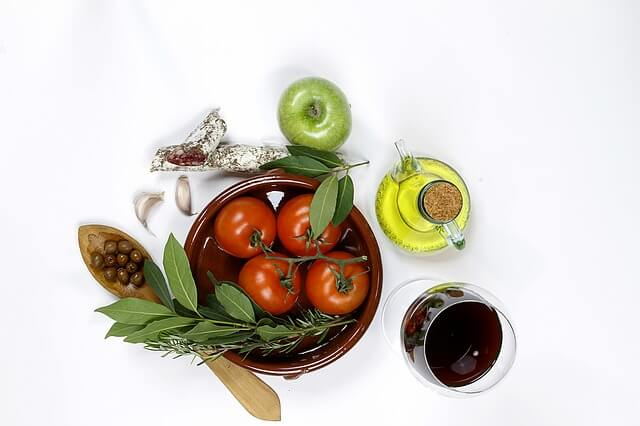 Pomidory, jabłko i oliwa na stole