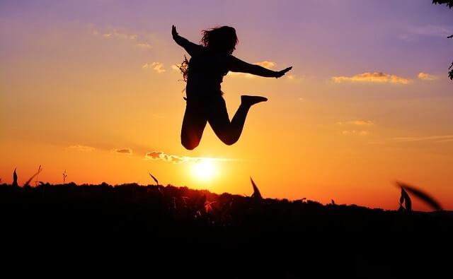 Sylwetka skaczącej kobiety na tle zachodzącego słońca