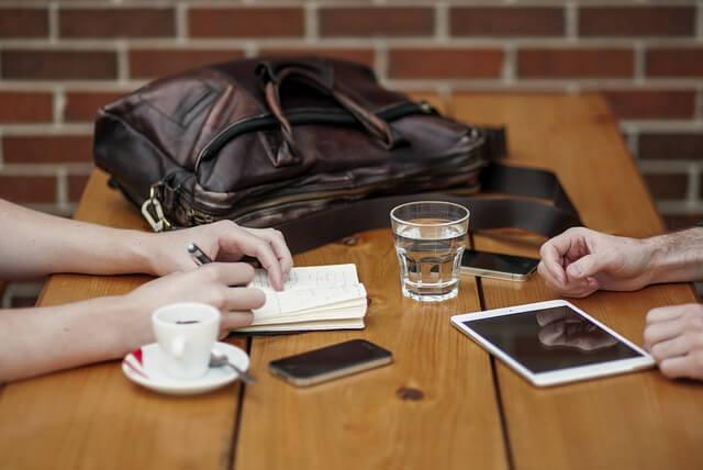 Dyskusja przy stole- lezy na nim torba, tablet, stoi szklanka