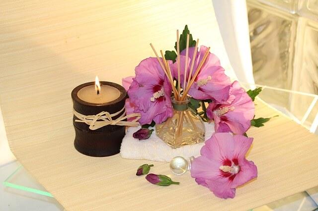 Zapalona świeca, dyfuzor z różowym kwiatami