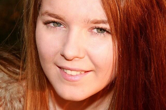 Brązowowłosa dziewczyna uśmiecha się w słońcu