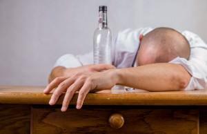 alkoholik na kacu z pustą butelką w ręce