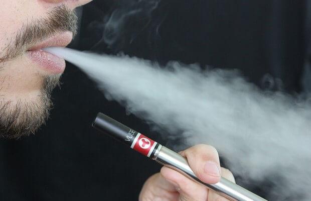 mężczyzna pali elektronicznego papierosa i wypuszcza dym
