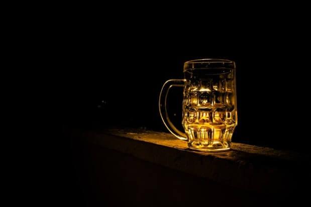 kufel z piwem podświetlony na czarnym tle