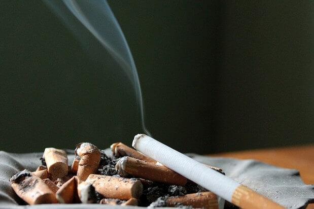 papierosy w popielniczce, z czego jeden jeszcze się kopci