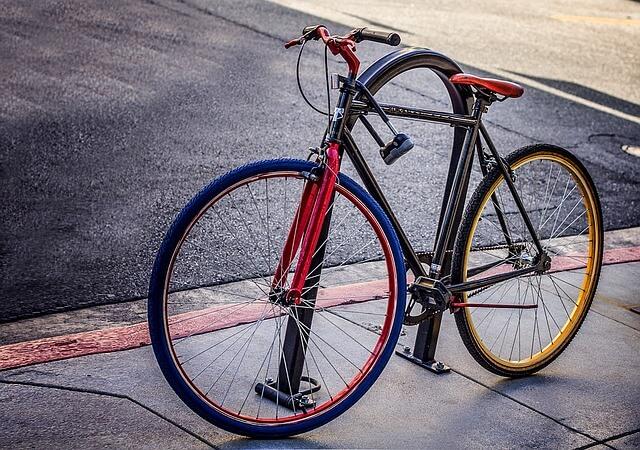 Kolorowy rower przypięty na chodniku
