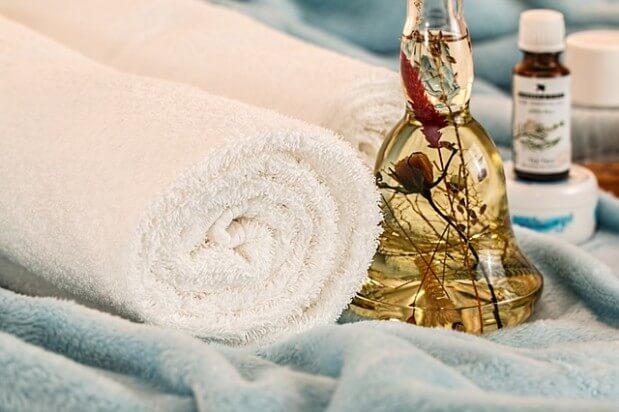 Olejek obok ręcznika i kremu